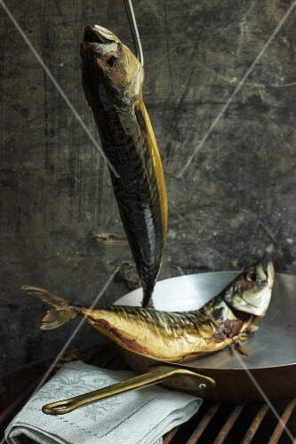 Smoked mackerel, one hanging and one in a copper pan