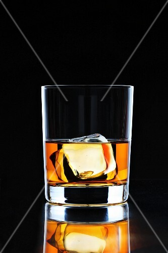 A glass of whiskey with an ice cube on a black surface