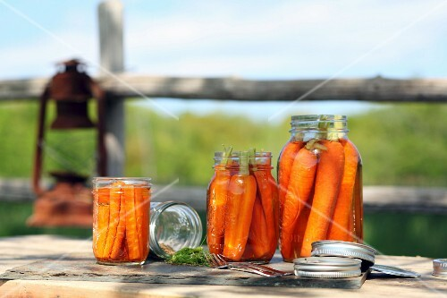 Carrots in preserving jars on a table outside