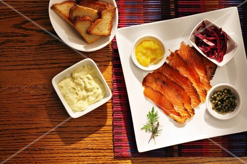 Slices of cured salmon with side dishes (seen from above)