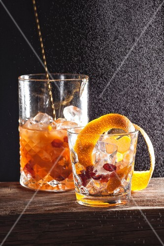 An alcoholic cocktail made with fruits and orange zest
