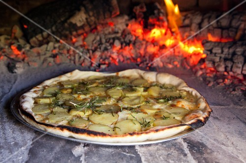 Potato and rosemary pizza baking in a pizza oven