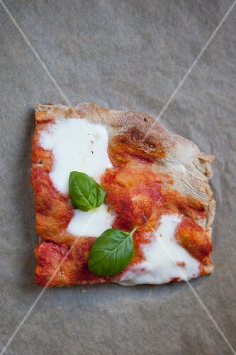 A slice of pizza with mozzarella, tomato and basil