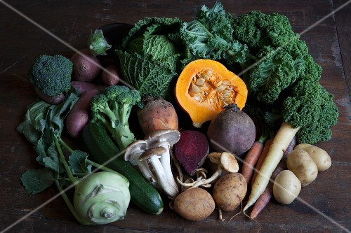 Fresh autumnal vegetables and mushrooms on a wooden table
