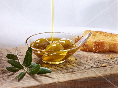 Olive oil being poured over green olives in a small dish