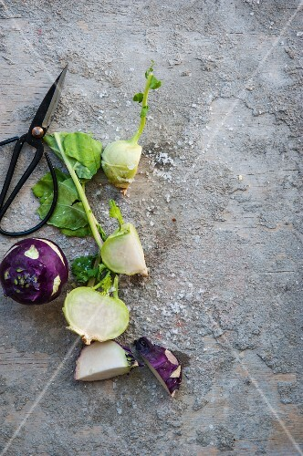 Green and purple kohlrabi on a stone surface