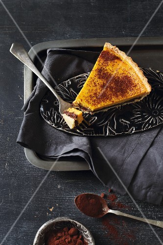 A slice of sweet pumpkin tart with chocolate cream and cocoa powder