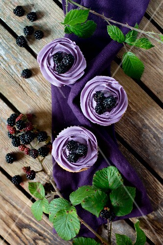 Blackberry cupcakes on a wooden table