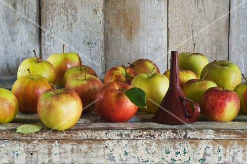 A funnel and Jonagold apples on a rustic shelf