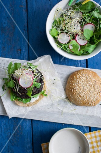 A vegetarian mushroom and millet burger with rocket, radishes, fresh bean sprouts and a yoghurt and horseradish sauce