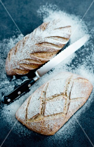 Bread dusted with flour with a bread knife