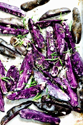 Purple potatoes with fresh herbs and olive oil on a baking tray