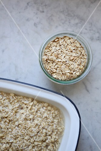 A jar of organic oats and softened oats in an enamel dish on a marble surface