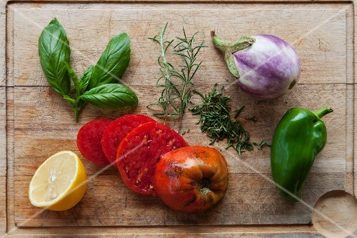 Fresh vegetables, herbs and half a lemon on a chopping board