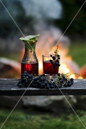 Homemade wine and red grapes with a campfire in the background