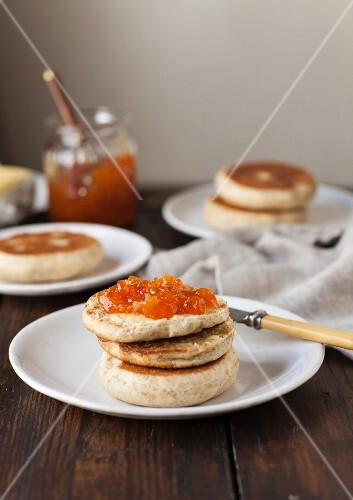 A toasted English muffin spread with jam