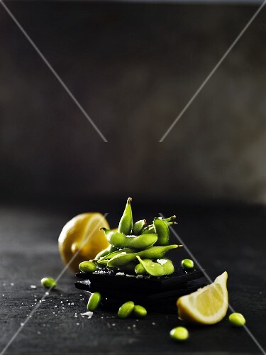 Raw soya beans with pods on a black slate platter with a sliced lemon