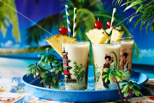 Pina coladas garnished with pineapple and cocktail cherries