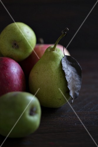 Pears and apples on a dark wooden surface