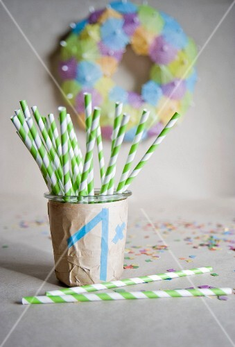 DIY children's party decorations: wreath of paper parasols & glass covered in brown paper