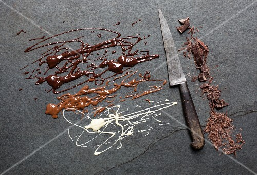 Melted and chopped chocolate on a grey surface