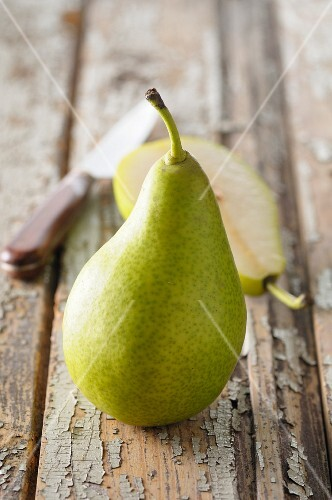 A whole pear and half a pear on a wooden surface