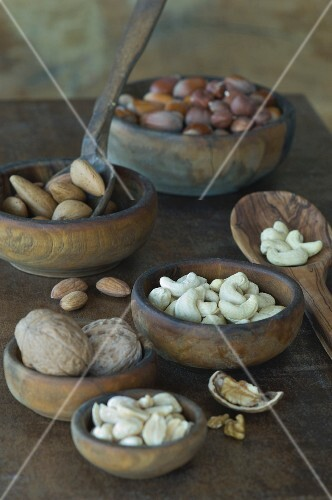 Various nuts with and without shells in wooden bowls