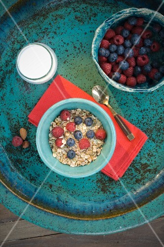 A healthy breakfast: muesli with fresh berries and milk (seen from above)