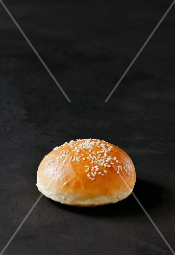 A burger bun with sesame seeds on a dark surface