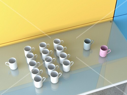 Coffee mugs of different colours on glass table