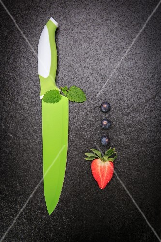 An arrangement featuring blueberries, a strawberry and green knife on a slate surface