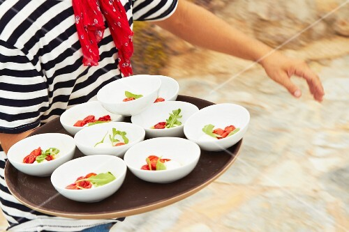 Bowls of mozzarella, tomato and basil being carried on a tray