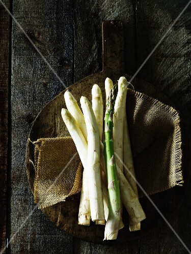 White and green asparagus on a rustic wooden paddle
