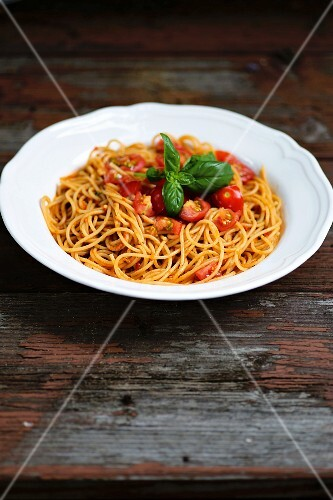 Spaghetti with fresh tomatoes on an old wooden table