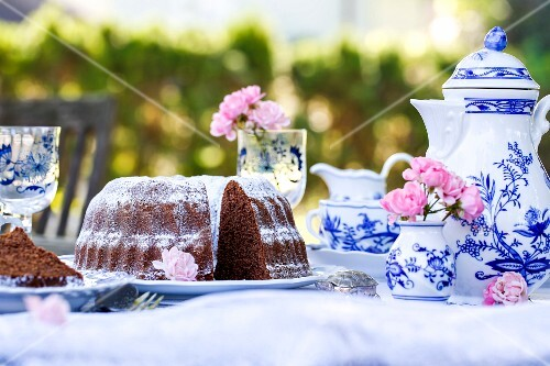 A sliced chocolate Bundt cake on a table laid for coffee in a garden