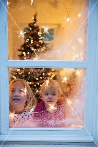 Sisters looking out of window decorated with artificial snow and fairy lights