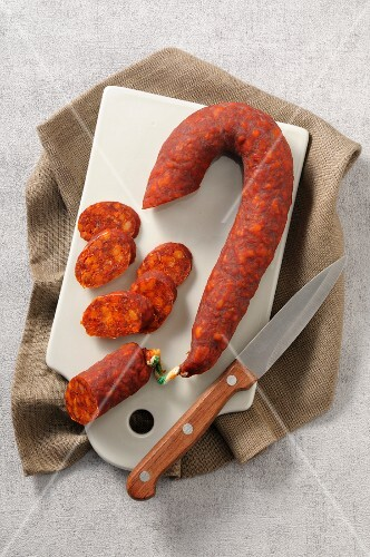 Spanish chorizo with a knife on a chopping board