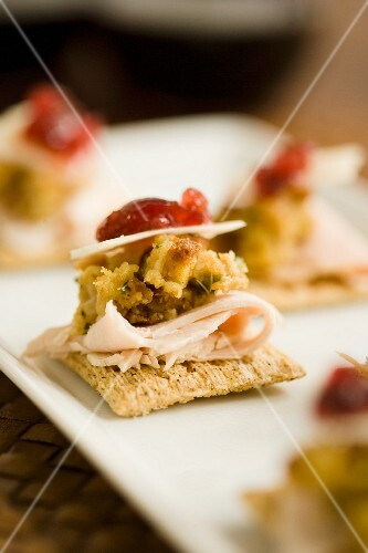 Crackers with turkey ham, vegetable cream, cheese and cranberry sauce