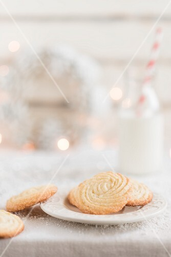 Simple homemade vanilla biscuits with a bottle of milk in the background