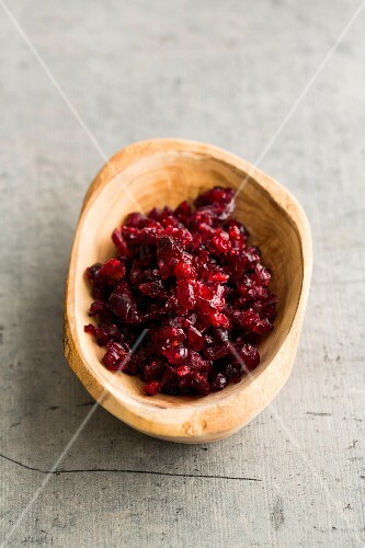 Chopped, dried cranberries in a wooden bowl