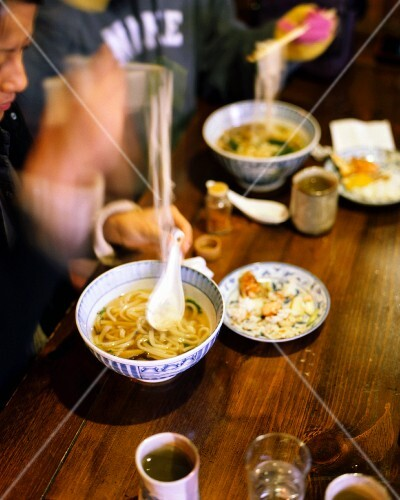 Guests eating noodle soup in a Japanese restaurant