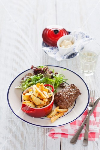 Beef steak with rosemary potatoes and frisee lettuce