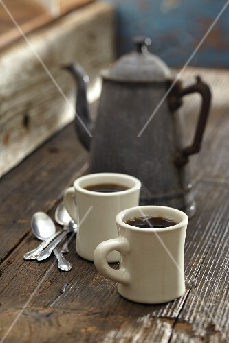 Two mugs of coffee with an old coffee jug in the background