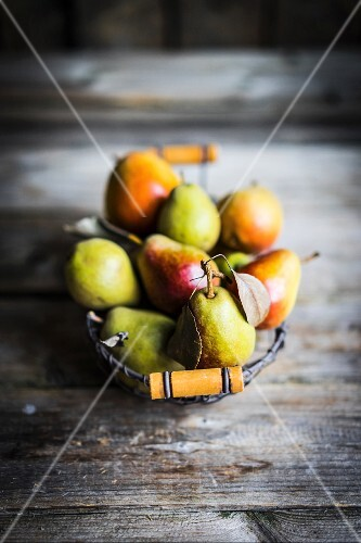 Autumn pears in a wire basket on a rustic wooden surface