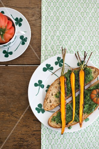 Slices of bread topped with pesto and roasted carrots on a plate with a clover leaf pattern