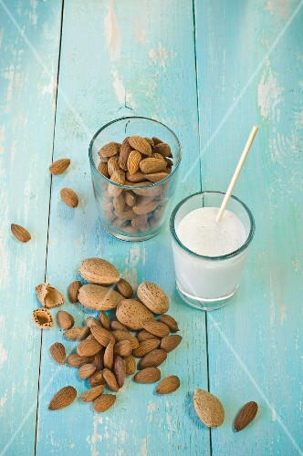 A glass of almond milk with a straw and a glass of almonds