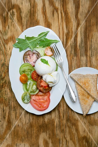 Burrata with heirloom tomatoes, rocket, olive oil and pepper on a porcelain plate served with toast
