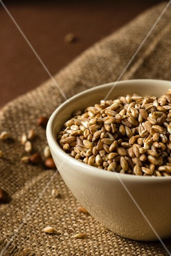 Spelt grains in a white bowl on a jute cloth