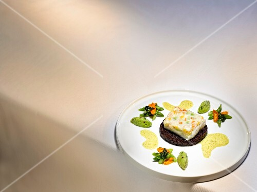 A dish by Dieter Müller: souffléd branzini with curry sauce, black rice and green asparagus