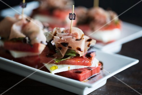 Stacks of watermelon and cheep's cheese with a slice of Parma ham with an olive oil and balsamic vinegar dressing